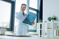 Serious handsome doctor talking on the phone. Interesting case. Serious smart handsome doctor looking at the X ray scan and talking on the phone while discussing stock photo
