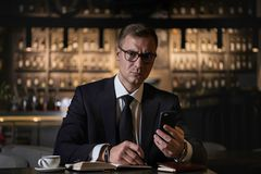 Serious handsome elegant businessman sitting at restaurant using his phone and writing the notes in his notebook. Serious handsome elegant caucasian businessman Stock Images