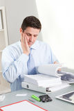 Serious Handsome Employee Reading Manuals. In the Office royalty free stock photo