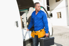 Serious handsome handyman holding toolbox Royalty Free Stock Images