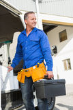 Serious handsome handyman holding toolbox Stock Image