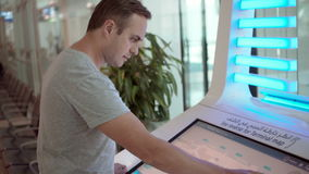 Serious handsome man in airport terminal. Using touchscreen, searching for flight information. Serious tired man in airport terminal. Using touchscreen stock video