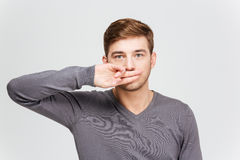 Serious handsome man in grey pullover covered mouth by fingers. Serious handsome young man in grey pullover covered mouth by fingers over white background royalty free stock photos