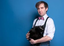Serious handsome man holding cute black cat and looking at camera. Serious handsome man in shirt, suspender and pink bow tie holding cute black cat and looking royalty free stock images