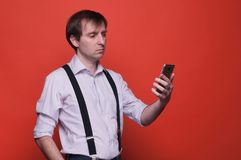 Serious handsome man in shirt with rolled up sleeves and black suspender standing and looking to smartphone on orange background w royalty free stock photo