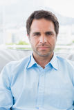 Serious handsome man sitting on the couch looking at camera Royalty Free Stock Photos