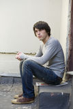 Serious handsome man sitting on on the doorstep. Stock Photo