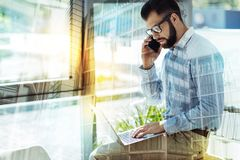 Serious handsome man talking on the cellphone and using laptop. Work conversation. Serious occupied handsome man sitting in the office on the table talking on Royalty Free Stock Photography