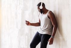 Serious handsome muscular african guy having relax time. Somber young athlete is leaning on wall and listening to music. He is holding player and using headphone Royalty Free Stock Photography