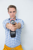 Serious handsome young handyman holding out drill royalty free stock image