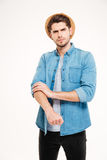 Serious handsome young man standing and rolling up his sleeves Royalty Free Stock Photography