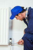 Serious handyman in blue coveralls repairing a radiator Royalty Free Stock Image