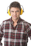 Serious handyman with earmuffs on white background Royalty Free Stock Images