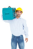 Serious handyman in hard hat carrying a toolbox Stock Photography