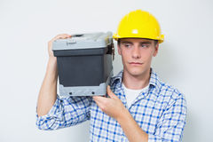 Serious handyman in yellow hard hat carrying toolbox Royalty Free Stock Photos