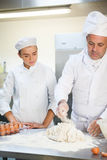 Serious head chef showing trainee how to prepare dough Stock Image