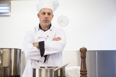 Serious head chef standing arms crossed behind pot. In professional kitchen royalty free stock images