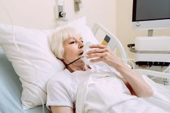 Sad woman taking off oxygen mask at hospital. Serious health problems. Exhausted retired lady looking sad while lying in a hospital bed and holding her oxygen Royalty Free Stock Photography