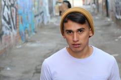 Serious hip Latino teen outdoors close up.  stock image
