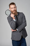 Serious hipster business man with magnifying glass Royalty Free Stock Image