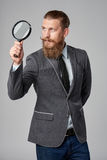 Serious hipster business man with magnifying glass. Serious hipster business man with beard and mustashes in suit looking up through magnifying glass, over grey Stock Photo