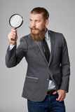 Serious hipster business man with magnifying glass Stock Images