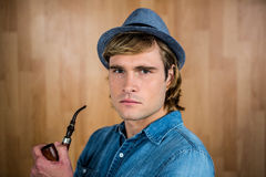 Serious hipster holding pipe Stock Photos