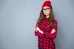 Serious hipster woman standing with arms folded Stock Image