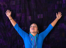 Serious Hispanic arms raised in exultation Royalty Free Stock Photography