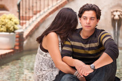 Serious Hispanic Couple During A Serious Moment. Attractive Hispanic Couple During A Serious Moment at a Fountain Stock Image