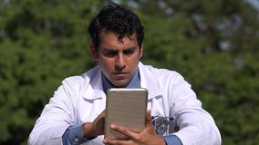 Serious hispanic doctor using tablet. A handsome adult hispanic man stock video footage