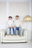 Serious husband and wife sits on back of white leather sofa Stock Photography