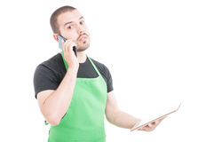Serious hypermarket clerk talking at phone and holding tablet Royalty Free Stock Image