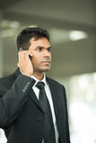 Serious Indian business man using mobile phone. Stock Photography