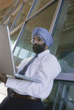 Serious Indian Businessman Using Laptop Royalty Free Stock Photos