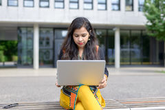 Serious Indian girl with laptop. Serious Indian girl with long dark hair sitting on stairs outdoors, holding laptop, looking at it stock photography