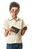 Serious intelligent child in glasses reading a book Royalty Free Stock Images