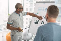 Serious intelligent man pointing at the picture. Professional explanation. Serious nice intelligent men standing near the whiteboard while pointing at the stock photos