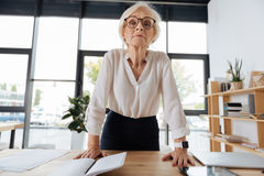 Serious intelligent woman leaning on the table royalty free stock photo