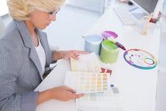 Serious interior designer looking at colour charts Royalty Free Stock Photos