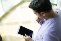 Serious issues, man looking at tablet Stock Images
