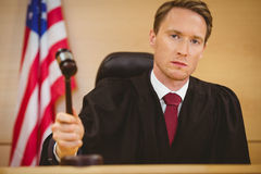 Serious judge about to bang gavel on sounding block Stock Image