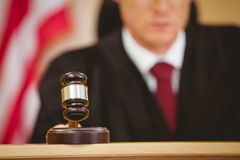 Serious judge about to bang gavel on sounding block Royalty Free Stock Photos