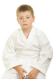 Serious karate kid sitting on knees Royalty Free Stock Images