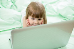 Serious kid girl lying on bed with notebook Royalty Free Stock Photo