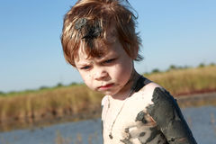 Serious kid in healing mud. Portrait of a serious kid in healing mud Stock Photos