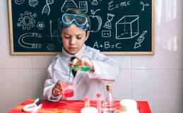 Serious kid playing with chemical liquids. Little boy scientist pouring chemical green liquid from flask against of chalkboard with drawings Stock Photos