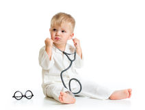 Serious kid playing doctor with stethoscope Royalty Free Stock Image