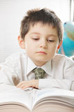 Serious kid reading book. Serious kid in white shirt reading book at desk Royalty Free Stock Photo