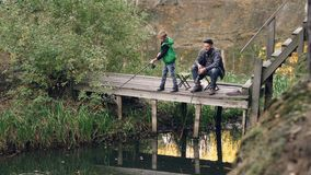 Serious kid is standing on wooden pier and fishing holding rod while his loving father is sitting on chair, catching. Fish and looking at his son with smile stock footage